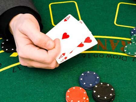 man hand holding two cards in the casino photo