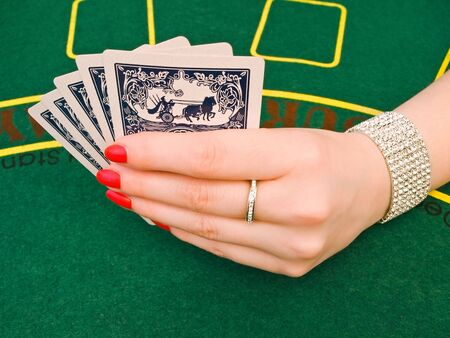 woman hand with jewelry holding playing cards