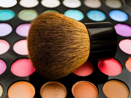 eyemakeup: multicolored eye shadows with cosmetics brush against the white background