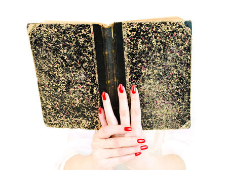 woman hands with red nails holding old book photo