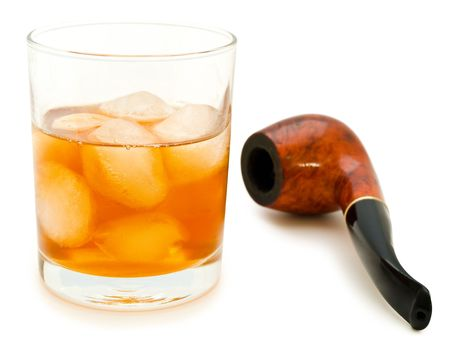 glass of alcoholoic drink with ice cubes and tobacco pipe  photo