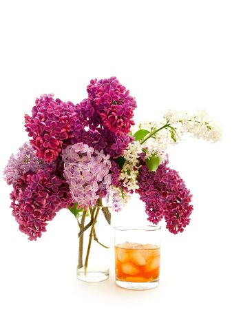 glass of alcoholoic drink with ice cubes and lilac photo