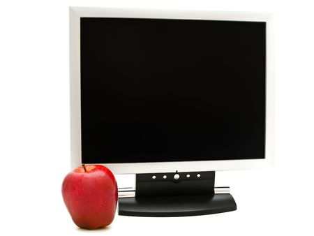 red apple near the monitor against white background photo
