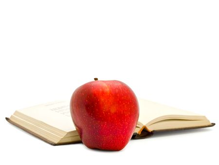 red apple next to the open book over white background photo