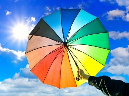 colorful cloudscape: milticolored umbrella in hand against blue sky Stock Photo