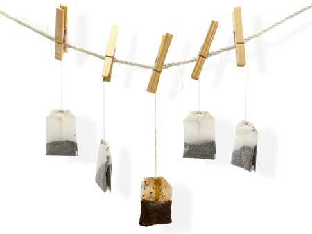 tool bag: drying tea bags at the peg against white background Stock Photo