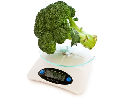 of the broccoli at electronic scales against the white background photo
