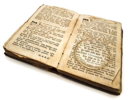 old bible with with magnifying glass over white background photo