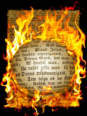 page from old book with text in flame photo