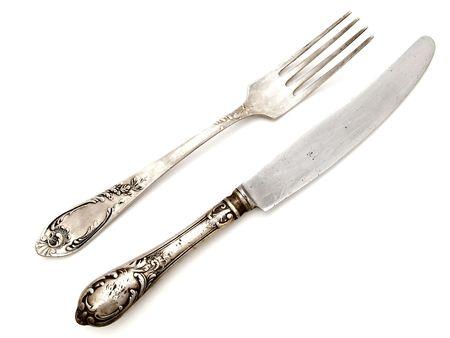 cubiertos de plata: viejo tenedor con el cuchillo sobre el fondo blanco