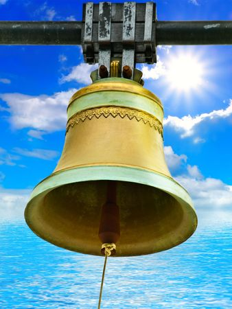 ding: Photo of the big bronze old bell against the water and blue sky with sun