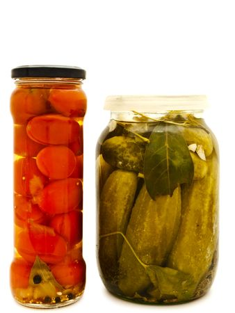 glass jars with marinated vegetables against the white background  photo