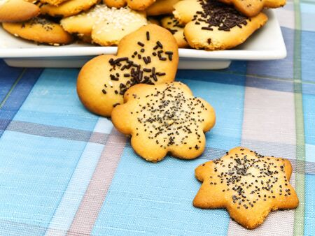 sweetie: home decorated biscuit scattered at blue tablecloth