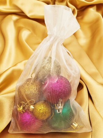 tissu or: D�corations pour arbres de No�l dans le sac de tissu blanc sur tissu or Banque d'images