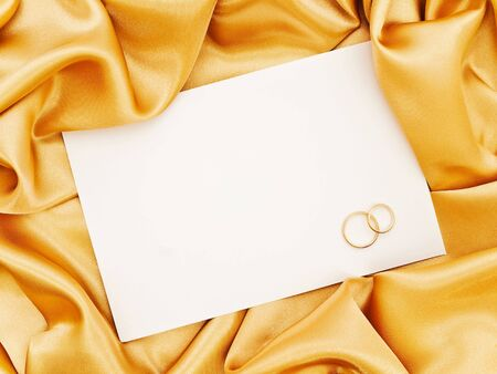 wedlock: Golden silk textile border round white paper with golden rings