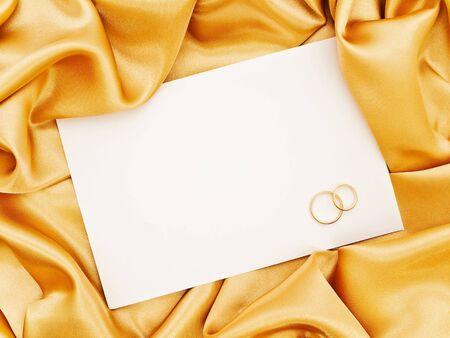 weddingrings: Golden silk textile border round white paper with golden rings