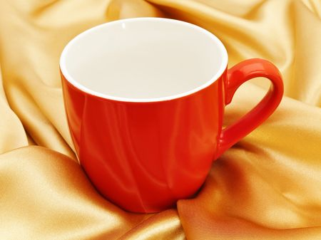 silken: Photo of single red mug at the golden fabric drapery Stock Photo