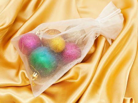 tissu or: D�corations pour arbres de No�l dans un sac de tissu blanc sur les gants d'or Banque d'images