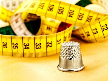 thimble against the multicolored measuring tape photo