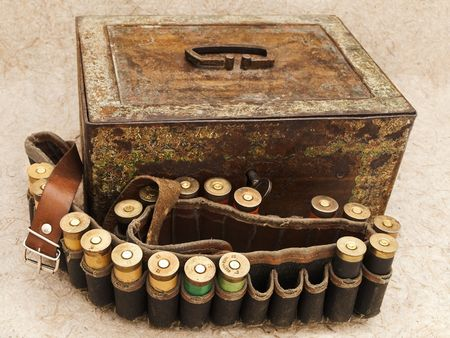 antique rifle: Photo of old cartridge for hunting rifle and vintage rusty chest against beige background