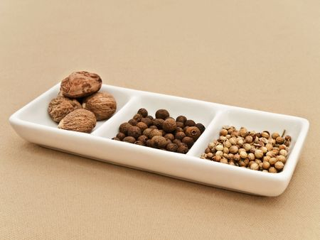 flavouring: Coriander, black pepper seeds and nutmeg in flavouring plate at beige textile