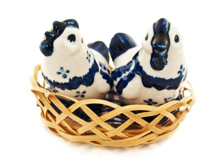 two porcelain chicken in wooden basket against white background photo