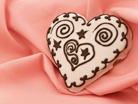 spice cake: spice cake in heart shape at pink textile drapery Stock Photo