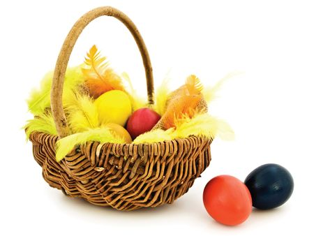 multicolored easter eggs and feathers in the basket with copyspace for your text photo