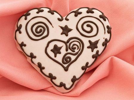 spice cake: Photo of spice cake in heart shape at pink textile drapery