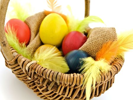 multicolored easter eggs and feathers in the basket photo
