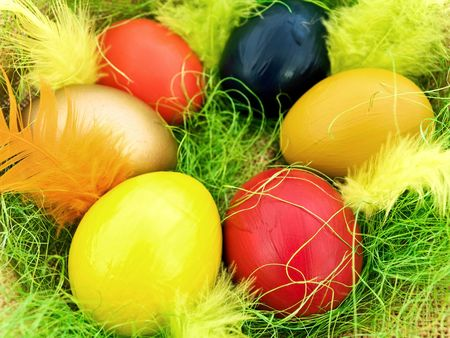 easter composition with multicolored eggs and feathers with green decoration photo