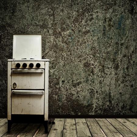 estufa: estufa de gas viejo sobre el fondo de pared de grunge