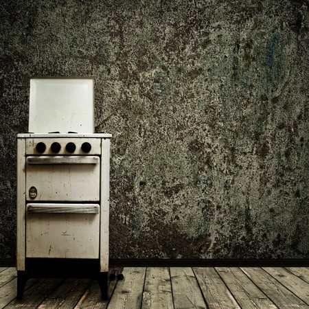messy kitchen: old gas stove over the grunge wall background