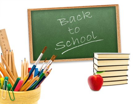 Back to school!  theme with red apple, stack of books and stationery against green blackboard photo