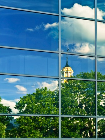 credence: church over blue sky reflection in clear windows of town