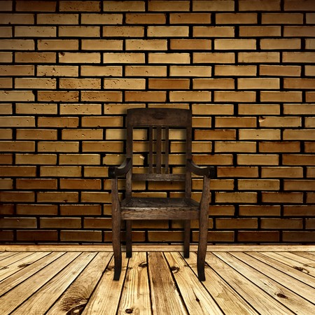 Single chair at wooden floor against beige brick wall photo