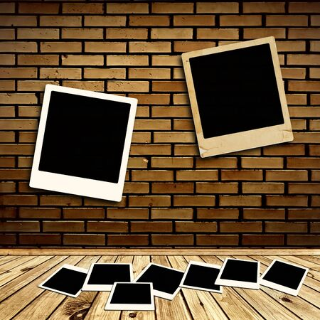 empty photo frames at brick wall and wooden floor photo