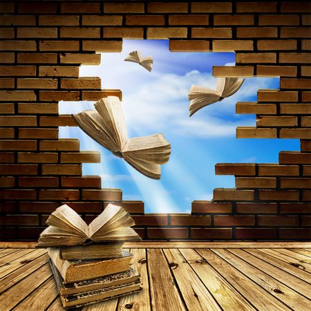 education concept: opened books flying through brick wall hole into blue sky
