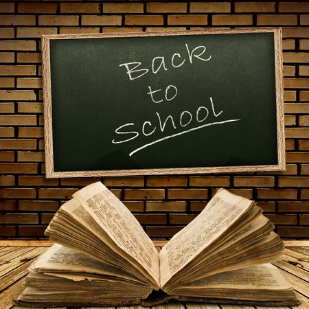 Photo of urban interior with school blackboard and opened vintage book