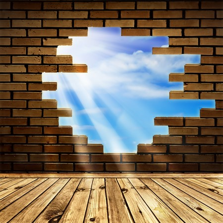 blue sky with sunlight  through the hole in the brick wall of room with wooden floor  photo