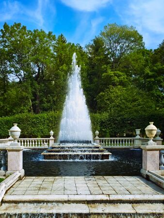 fountainhead: stage fountain in the park over green trees and blue sky, Peterhof, St. Petersburg