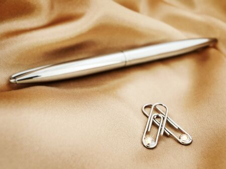 ball pen: shiny clips and ball pen over the gold textile (shallow DOFF)