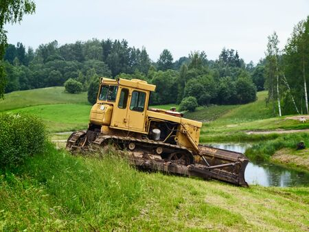 bagger: old yellow single tractor at green meadow near pond