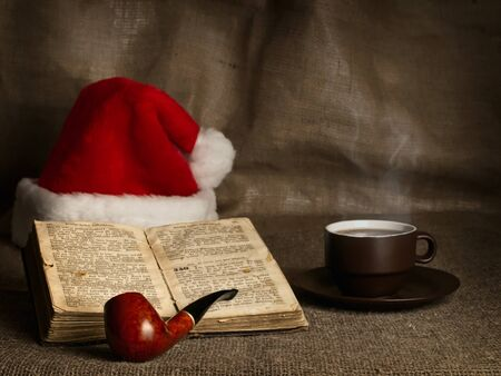 new books: Christmas and New year theme with open Bible , cup of tea, Santa`s hat and pipe