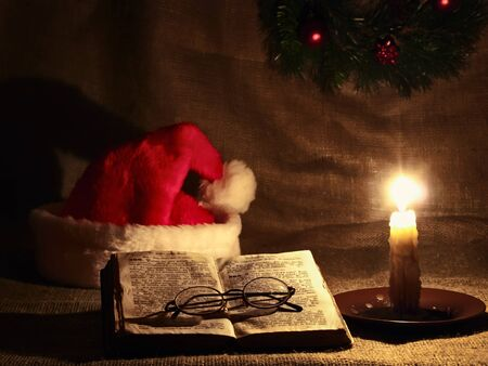 Christmas and New year theme with open Bible, candle, Santa`s hat and garland photo