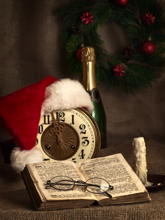 Christmas and New year theme with open Bible, vintage clock, candle, champagne, Santa`s hat and garland  photo