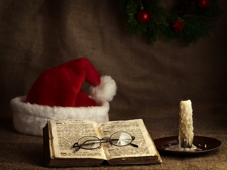 Christmas and New year theme with open Bible, vintage clock, candle, Santa`s hat and garland photo