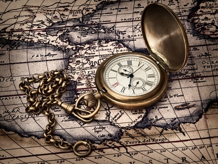travelling theme: vintage clock at antique map