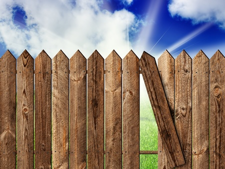 wooden fence over the backyard with sky and sun photo