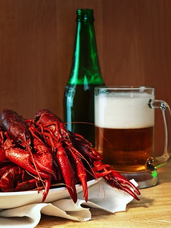 red boiled crawfishes and mug of beer  photo